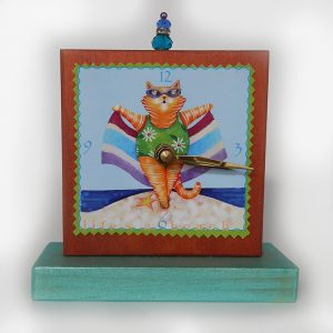 "The Beach Cat Precious Time Shelf Clock is hand painted in copper and aqua shimmery color. It has my beach cat image and says ""life's a beach"". Bead detail on top."