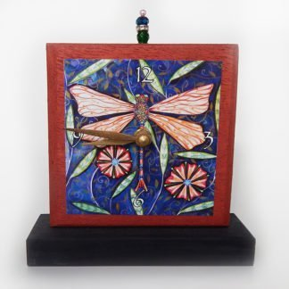 Danasimson.com Dragonfly Precious Time Shelf Clock is painted copper color with a black base- It has a dragonfly image on a deep blue background with scattered flowers. A glass bead detail is at the clock's top.