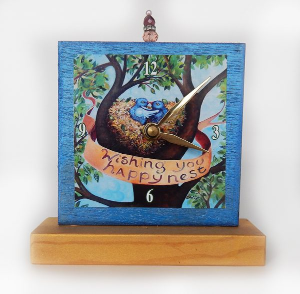 Happy Nest Precious Time Shelf Clock is blue and gold with two birds in a nest in a tree- it says wishing you happy nest on a banner.