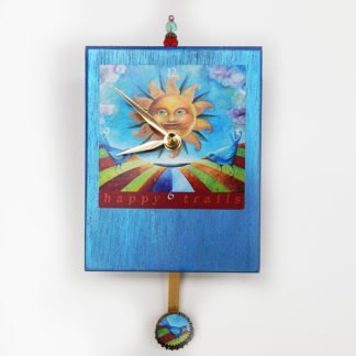 Danasimson.com Happy trails Precious Time Clock has a smiling sun image on a shimmery blue wooden clock body. A blue bird of happiness is on the bottle cap pendulum.