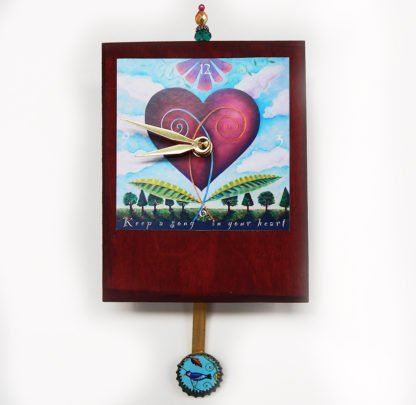 Danasimson.com Heart Precious Time Clock has a heart blooming in a garden image and a blue bird in the bottle cap pendulum- the clock body is a deep wine color and has a bead detail at the top.