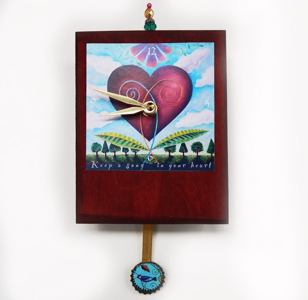 Heart Precious Time Clock has a heart blooming in a garden image and a blue bird in the bottle cap pendulum- the clock body is a deep wine color and has a bead detail at the top.