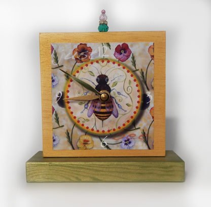 Danasimson.com Just Bee Precious Time Shelf Clock has a gold and green wood body with a honey bee surrounded by winter pansies. There is a bead detail at the top.