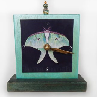 Danasimson.com Luna Moth Precious Time Shelf Clock is shimmery aqua and deep forest green with a luna moth on a black background image. A glass bead detail is at the clocks top center.