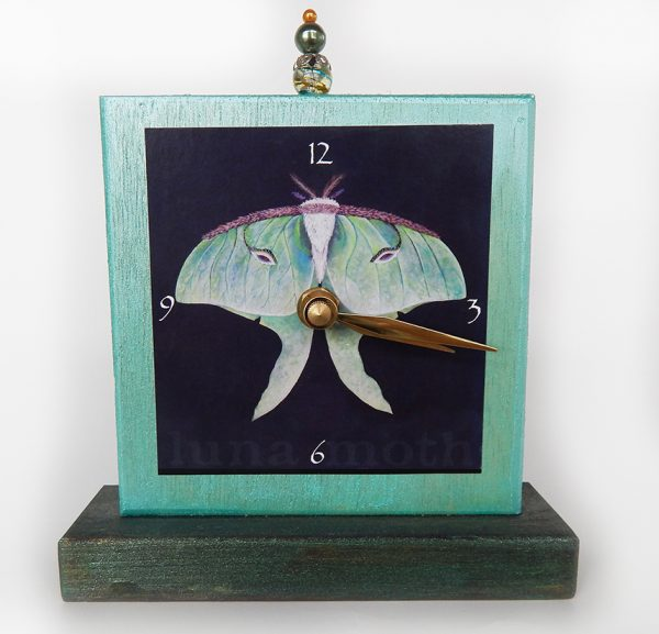 Luna Moth Precious Time Shelf Clock is shimmery aqua and deep forest green with a luna moth on a black background image. A glass bead detail is at the clocks top center.