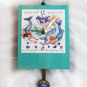 Mermaid Precious Time Clock shows 4 mermaids swimming with shells and fish. The wooden clock body is aqua. There is a crab or fish in the bottle cap pendulum