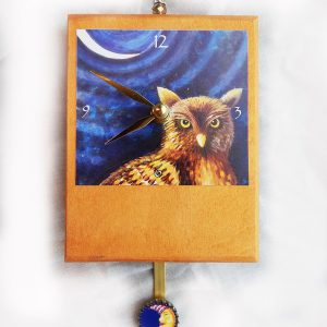Night Owl Precious Time Pendulum Clock has a hoot owl under a sliver moon-there is a small moon face with a night cap on the bottle cap pendulum the wooden body of the clock is painted metallic gold.