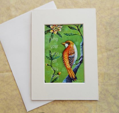 """Danasimson.com Matted art card with envelope, """"Sing your song, all day long"""" quote, golden bird image."""