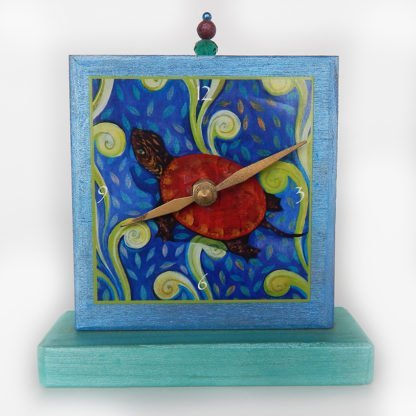 Danasimson.com Turtle Precious Time Shelf Clock is hand painted shimmery blue and aqua on a wooden base, an archival print of the Red Turtle is the clock face.