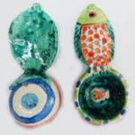 """front and back Our handmade Fish handle Coffee Scoop is about 7 inches by 3,"""" in colorful ceramic. The handle is a raised design of a fish. A smaller fish is in the bowl of the scoop."""