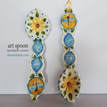 Danasimson.com handmade folk artDragonfly & Daisy Ceramic Spoon is cut out, formed in clay and individually decorated using my handmade stamps. The raised imagery detail includes a daisy in the spoon area and dragonfly on the handle.