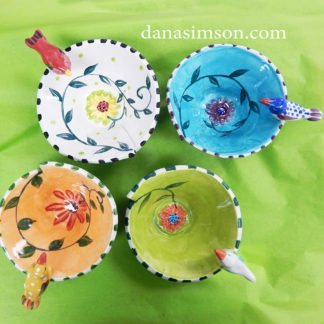 A set of four different colored Bird Bowls looking down to see the daisy and vine design painted on each interior.