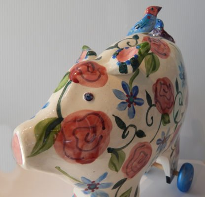 Danasimson.com Large pig sculpture with floral pattern on wheels.