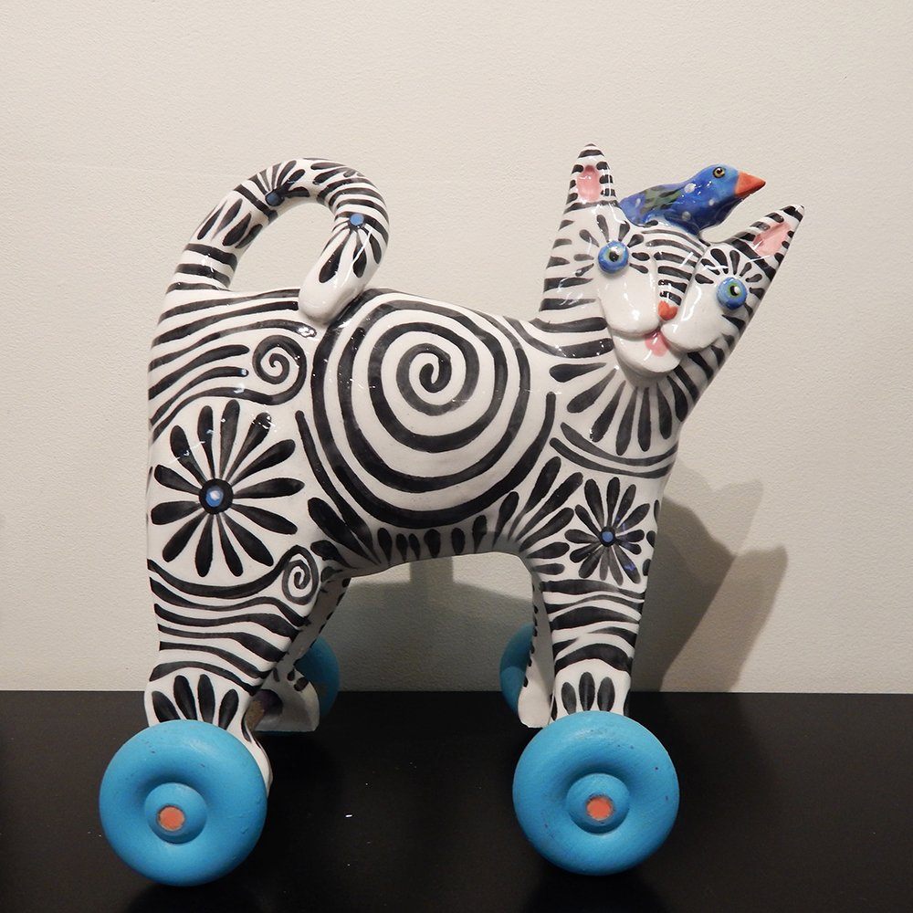 Folk art toys Danasimson.com Hand built folk art toy black and white striped cat with bird on head on wooden wheels.