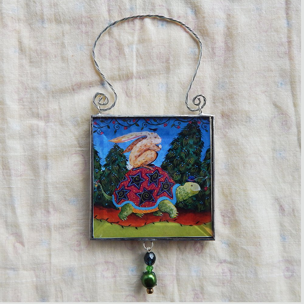 Danasimson.com The Journey is the thing, double sided beveled glass ornament with a hare riding on a tortoise image. Twisted wire handle and bead detail.