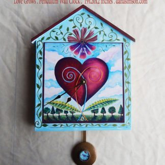 Danasimson.com Love Grows Wall Clock is hand painted light blue with vines all over. the main heart growing in a garden image is a print on the house-shaped wooden clock. It has a pendulum.
