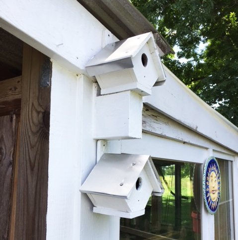 two fixed wooden birdhouses on a barn