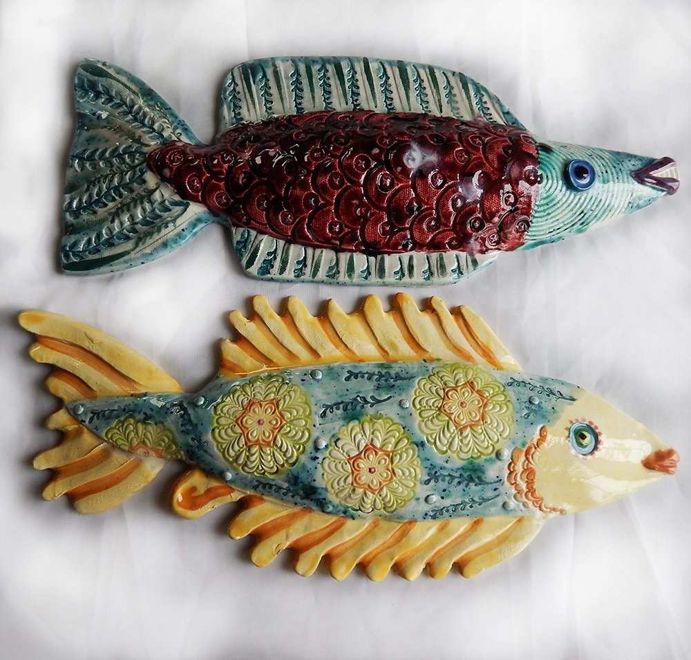 two intricately decorated ceramic fish