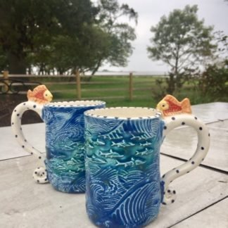 mugs with big tsunami waves and fish all over them